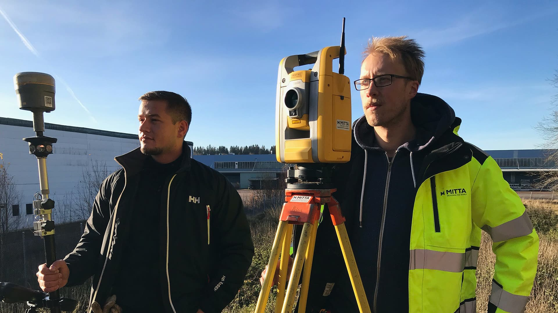 Two men stand outside with surveying service machines